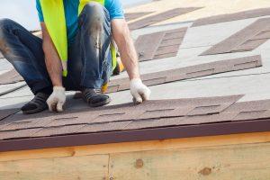 Roofer builder worker installing Asphalt Shingles